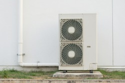 Close up Air conditioning out door,A group of three industrial sized air conditioners along a brick wall,Air conditioning with extra door for maintenance