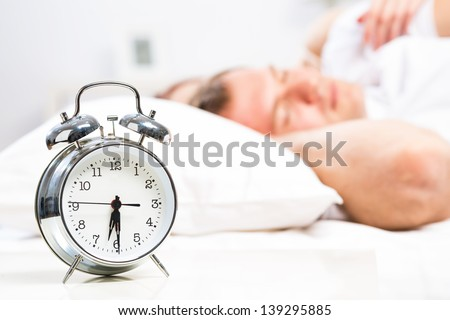 close-up alarm clock next to the sleeping people