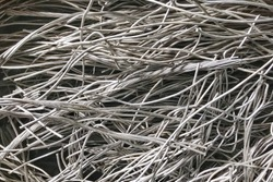 Close up aluminums wire scrap metal for recycling or reproducing in the melting foundry. Aluminums raw material are reused in the industry. Non-ferrous scrap in the waste recycle manufacture.