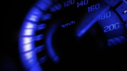 Close up and blurred mile indicator of a speed meter in a car with blue light speed at 180 Km/H in concept racing car