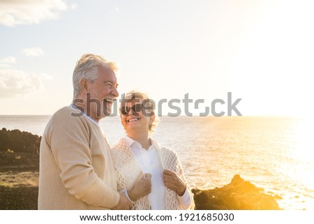 close up and portrait of two happy and active seniors or pensioners having fun and enjoying looking at the sunset smiling with the sea - old people outdoors enjoying vacations together
