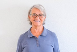 close up and potrait of mature woman smiling and looking at the camera with a white wall at the background - active senior concept and lifestyle