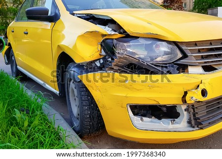 Close-up and selective focus of a badly broken yellow taxi car with torn, crumpled and scratched parts after a major accident. The concept of the need for car and life insurance. Mobile photo. Stock photo ©