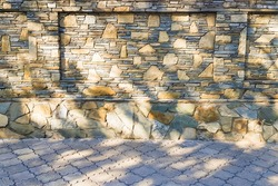 Close-up and selective focus of stone fence made of sandstone laid out with mosaics and asphalt tiles in foreground on sunny day with shade from foliage. Concept of arrangement of house territories