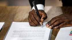Close up and selective focus on African black formal professional business male hands holding pen, signing in white paper form or application to confirm and deal contract agreement on table