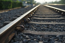 Close up and selective focus photo of railway track or railroad or rel kereta api with morning sunlight.