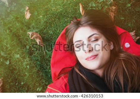 Close-up and top view of woman sitting in the green grass with her eyes closed.