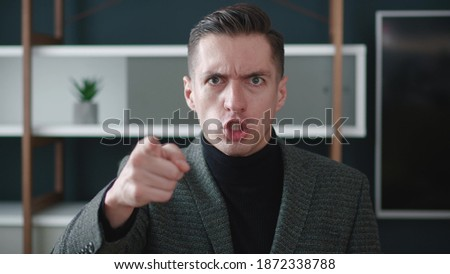 Close-up angry businessman shouting and pointing at camera. Portrait of aggresive boss scolding and shouting at employees threatening with a finger and shouting at the camera. Stock foto ©