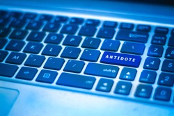 Close up antidote/ health concept - ANTIDOTE on the key command of the keyboard glowing in blue colour as the symbol of hope. Selective focus.