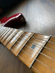 close up apple red scallop electric guitar neck and nickel stings on veneer wood background with copy space for letter in Vertical photo. business and music concept. Wallpaper or background for book.