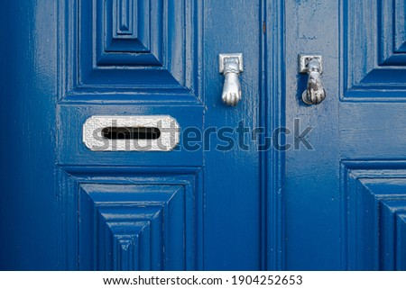 Close-up architectural design detail of blue wooden house entrance door panels in traditional pattern with metal letterbox and door knockers in Portugal Stock photo ©