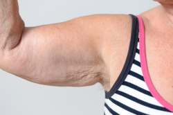Close up Arm Muscles and Underarm of a Middle Aged Woman in Casual Sleeveless Shirt, Isolated on Gray Background.