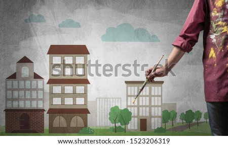 Close up artist hand holding paintbrush. Painter in shirt standing on background colorful picture of city. Summer cityscape with high buildings artwork. Creative hobby and artistic occupation.