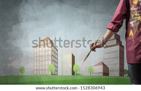 Close up artist hand holding paintbrush. Painter in shirt standing on background colorful picture of city. Modern downtown with high office buildings artwork. Creative hobby and artistic occupation.
