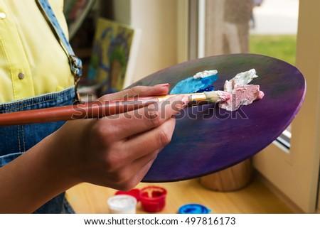 close-up artist mixes paint brush on an easel. #497816173
