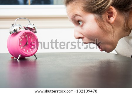 Close up as a young woman gapes at a pink alarm clock in shocked panic
