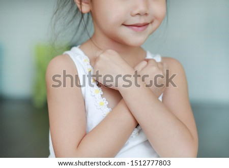 Close up Asian child girl with cross one's arm for confident. Emotion confident concept.