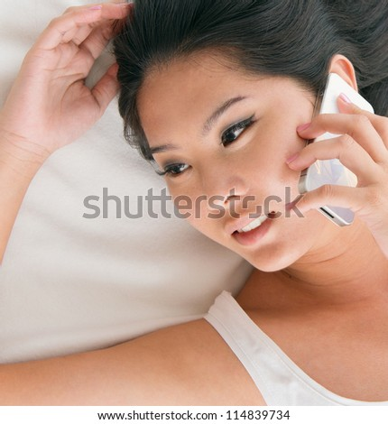 Close up Asian female talking on phone on her bed