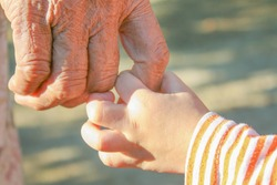 Close up asian grandmother and grandchild holding hands