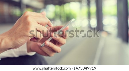 Close up asian man using smart phone mobile device for play or shopping online or check time and date , teenager with technology concept