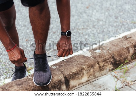 Close up Asian sport runner black man wear watch stand step on the footpath trying shoelace running shoes getting ready for jogging and run outdoor street health park, healthy exercise workout concept Foto stock ©