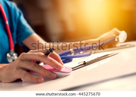 Close up asian woman doctor working in hospital using computer mouse and holding stethoscope to check for virtual patient, vintage tone with sunlight effect picture.