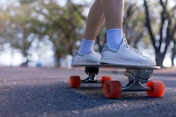 Close-up Asian women surf skate or skateboard outdoors on beautiful morning. women play surf skate at park on morning time. Close up Asian women leg wear sneaker paly surf skate on public park. Sport