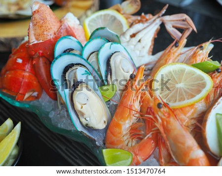 Close up assorted fresh cooked cold seafood as shrimps, prawns, New Zealand mussels, mussels, oyster, rock lobster, lobster claw with yello leomon in oval shaped dish or plate on ice on wooden table #1513470764