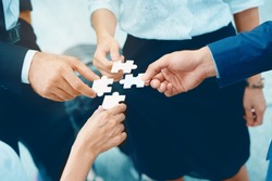 Close up at a businessman holding hands. Four puzzles come together. It represents teamwork. Must have understanding in working in the same direction in order to fully and effectively work.