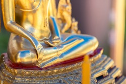 Close-up at a golden bronze buddha statue's hand in meditation action, religion abstract photo. Selective focus at hand part.