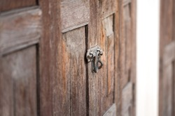 Close-up at aged wooden door which is locked by rusty metal hasp. Vintage style building and background photo. Selective focus at the metal part.