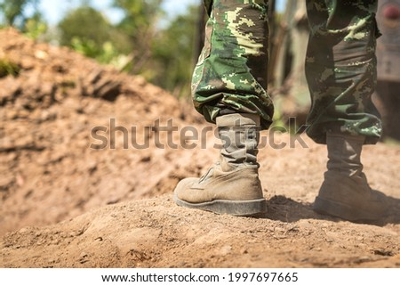 Close-up at combat shoe of a  infantryman soldier who wearied camouflage uniform during  standing on the battlefield ground. Selective focus at part of the shoe. Stock photo ©
