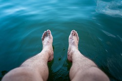 Close-up at human bare foot which is soaking in clearly turquoise water for relaxing. Travel and holiday vacation abstract photo concept.
