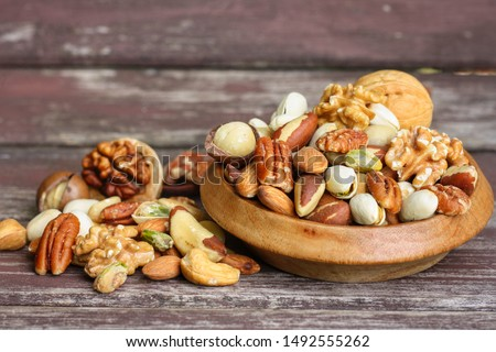 Close up at Mix nuts in wooden plate on wooden table background.Nuts including Cashew,walnuts,almonds, brazilian nuts,pecan and macadamia.Intake a handful of nut a day can stave off various disease.