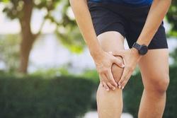 Close up athlete man, Knee pain after exercise .It happens often in athletes practice overtain.In arthritis concept.