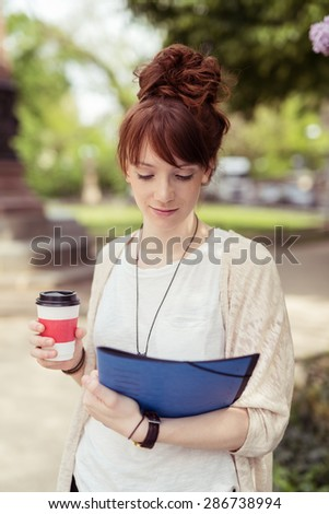 Close up Attractive Girl Student Holding a Cup of Coffee While Reading Something on Top of the File Folder on her Other Hand.