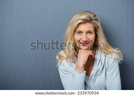 Close up Attractive Mature Woman, with Blond Hair, Posing with Hand on the Chin. Captured with Gray Wall Background.