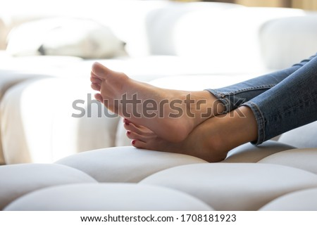 Close up attractive young woman legs lying on sofa. Beautiful female smooth foot relaxing on couch at home. Girl enjoying soft skin, foot rest and skincare cosmetics, no shoes concept. Stockfoto ©