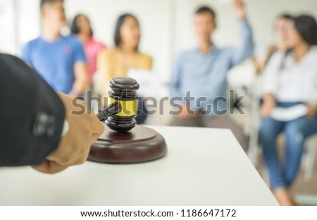 Close up auctioneer hand, black suite, holding gavel, wooden hammer, and blur group of people in auction room, one man raising hand up for bidding. Product or project auction market concept background