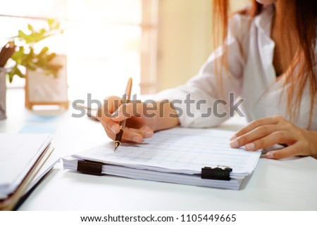 Close up audit woman calculate on paper document financial data.