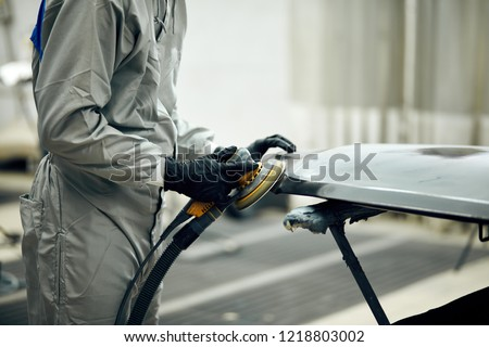 close up, Auto mechanic grinds car part for painting. Car body work auto repair paint after accident