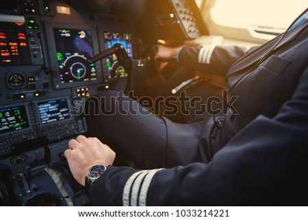 Close up aviator hand working with aircraft appliance in cockpit. Appliance and job concept #1033214221
