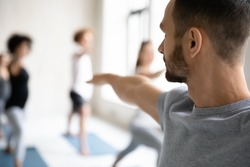 Close up back rear view young focused professional fit male trainer giving master class to group of students, showing warrior second virabhadrasana II position to motivated people in modern studio.