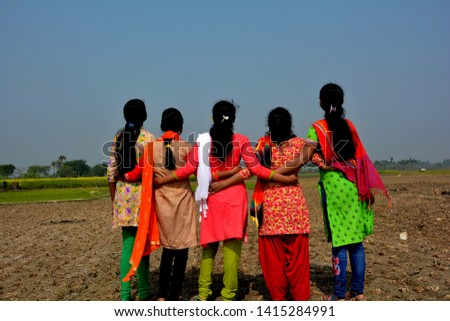 Close up back shot of five young girls, teenagers wearing colorful salwar kameez dress, looking up to the blue sky in a harvested field with the hands interlocking their waist in unity, conceptual pic