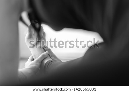 Close-up back view of a young woman reaching out for her right foot on a head-to-knee forward bend asana or yoga pose. Black and white horizontal view. #1428565031
