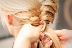 Close up back view of female hands braiding a pigtail to young blond woman at beauty salon