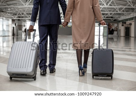 Close-up back view of legs of enamored businesswoman and businessman are going along airport lounge. They are holding hands while carrying their suitcases to departure area #1009247920