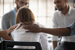 Close up back view unhappy woman with supporting diverse people at therapy session, touching shoulders, sitting in circle. Stressful businesswoman getting psychological help, trust and support.