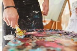 Close up background image of unrecognizable male artist putting paint on palette while painting pictures in art studio, copy space