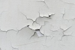 Close-up. Badly fixed building facade wall covered with cracks in stucco and paint. Missing patch of paint in the middle; crack with flappy peeling edges.